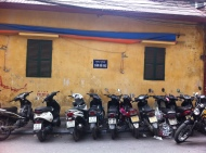 Motorcycles and mopeds parked under a no parking sign in Hanoi, Vietnam